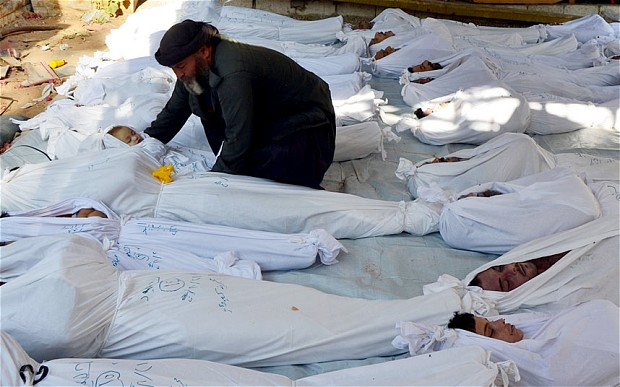 A+man+cradles+the+body+of+a+dead+child+amongst+the+bodies+of+dozens+of+others+in+Damascus+