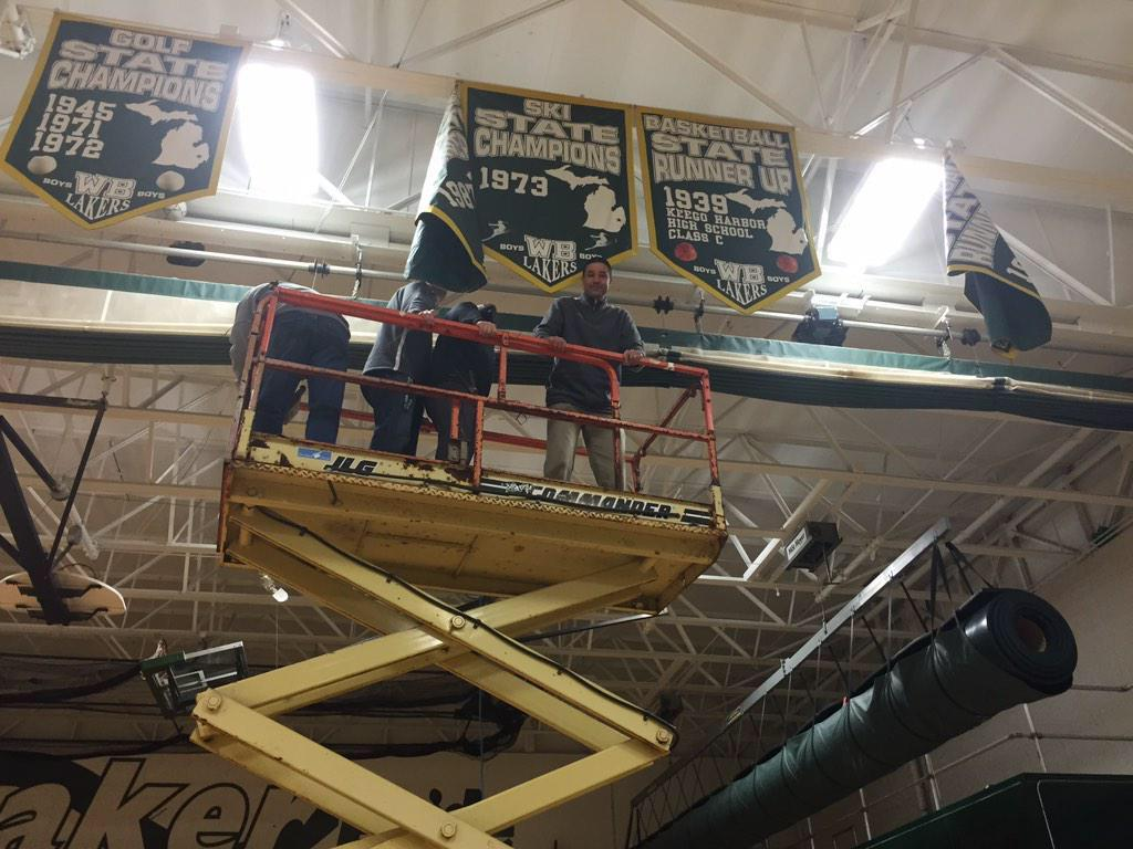 The WBHS Administration hangs the Cheer teams banner for their 1st place prize at districts.