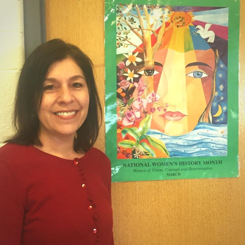WBHS Social Studies and Leadership teacher Ms. Jennifer Sepetys wears red in support of International Women's Day, alongside her Women's Month poster.