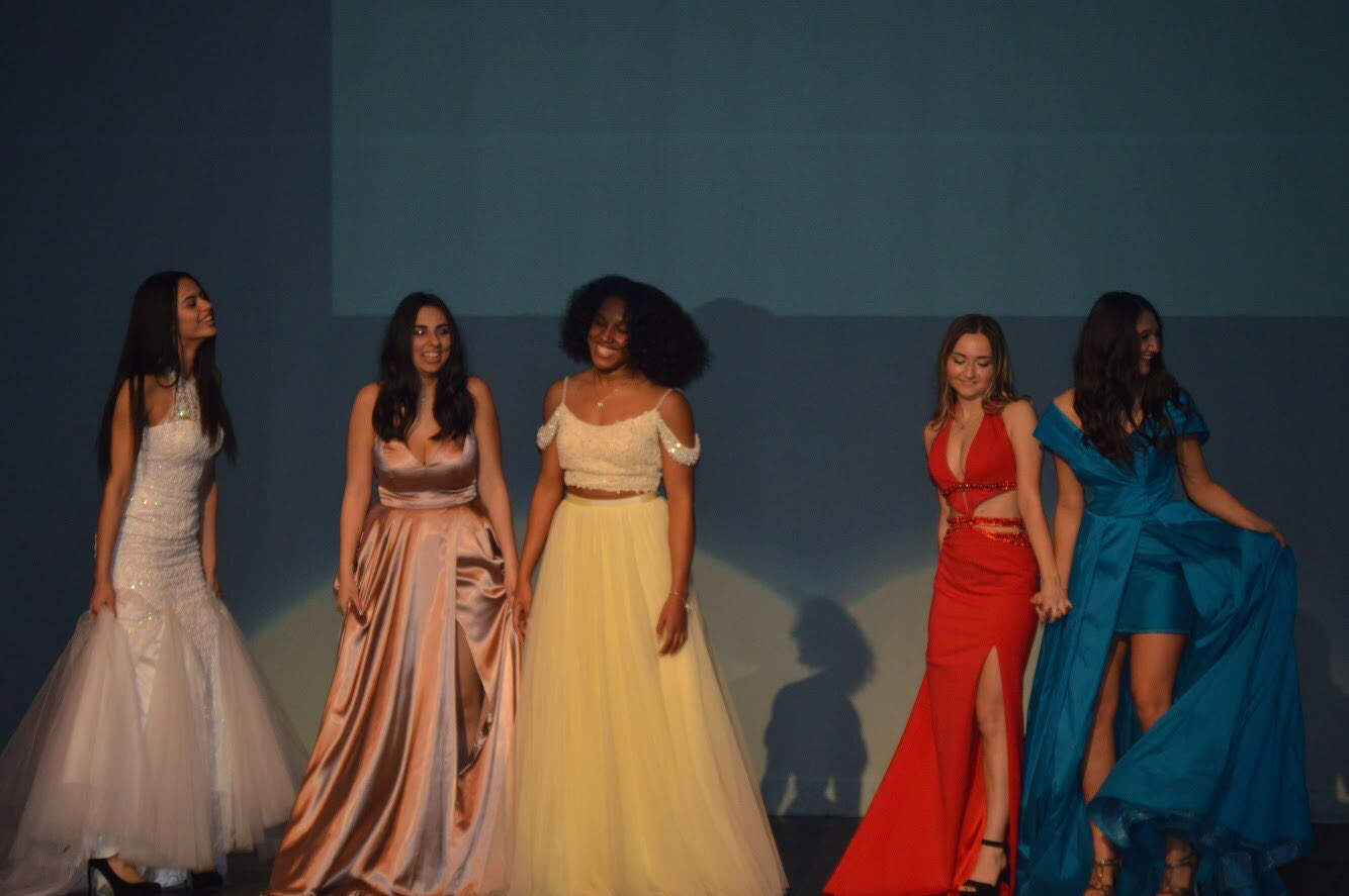 Fashion students modeling prom dresses from Hermz Boutique.