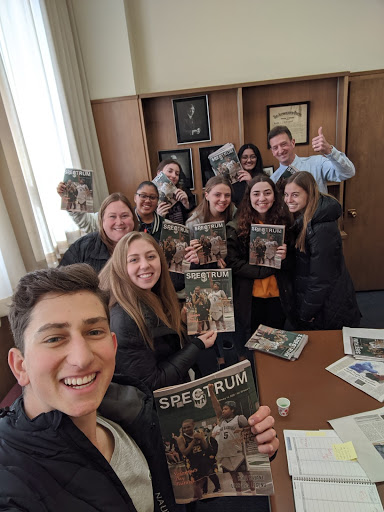 Spectrum news staff hold up their freshly printed copies of the latest edition.